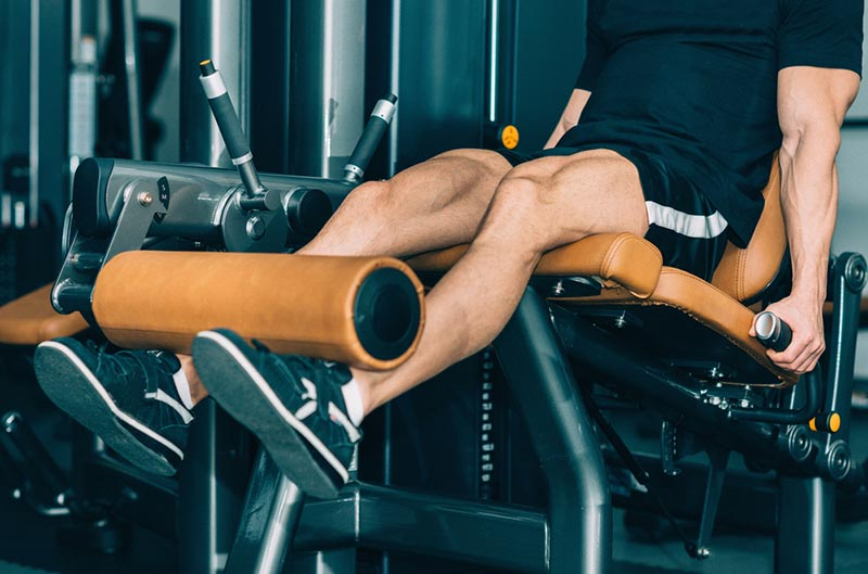 Man Working Out Using A Leg Extension Machine For Fitness
