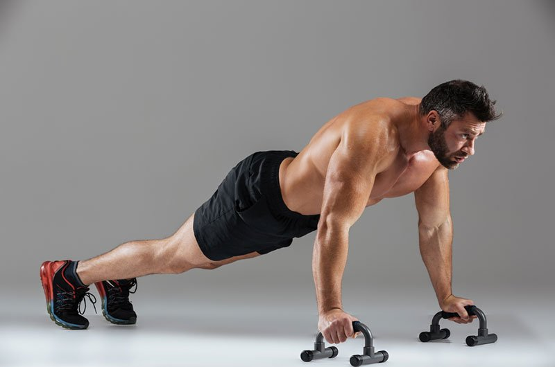 Fitness Man Working Out Using Push Up Bars