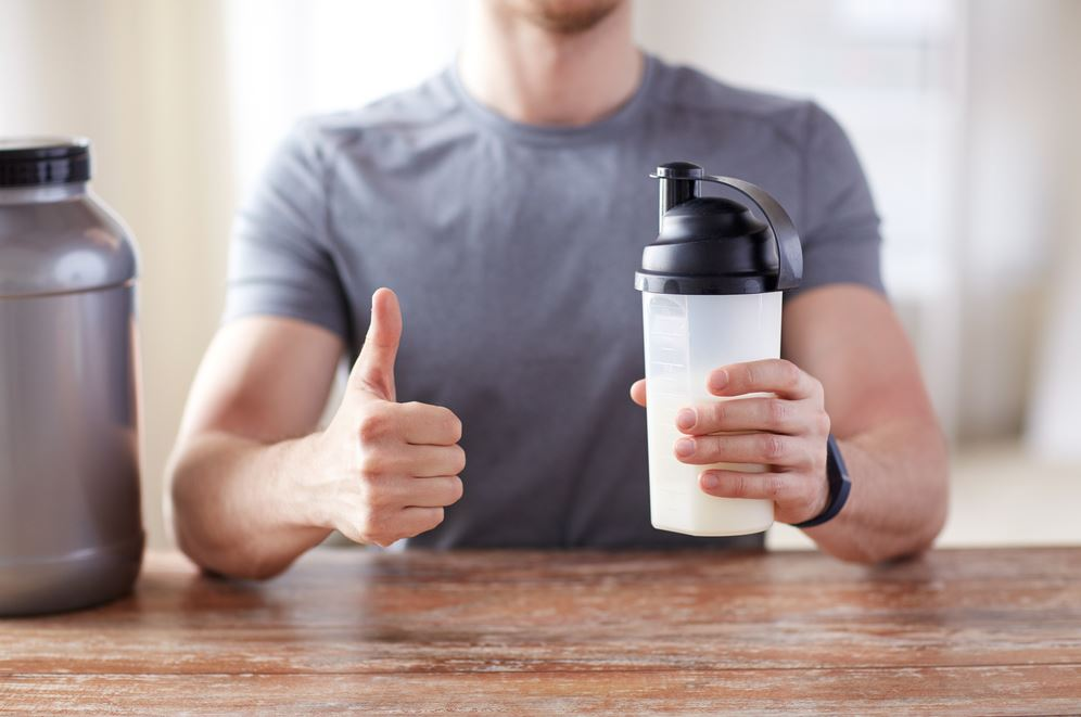 Man holding shake bottle with supplement