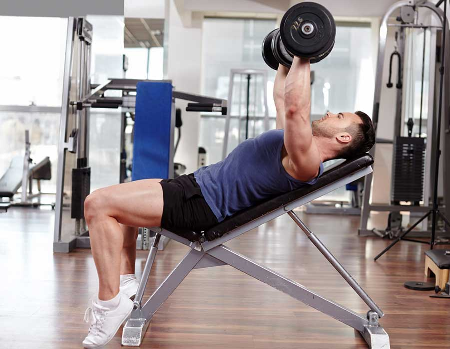 Man Lifting Dumbbells Using Weight Bench