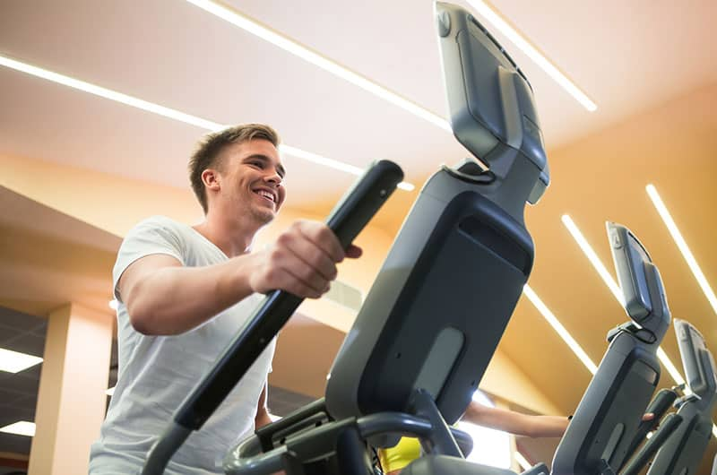 Fitness Man Working Out Using Elliptical Machine